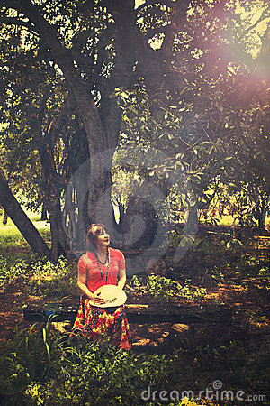Woman sitting on the bench by the tree