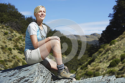 Woman Sitting On Boulder In Forest