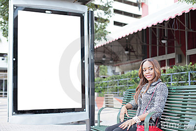 Woman sitting at a bus stop bench