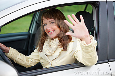 Woman sitting in the car and waving