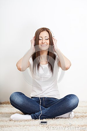 Woman sitting on carpet and listen to the music