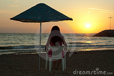 Woman sitting on chair and admire sunset