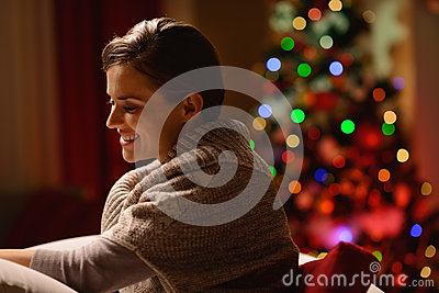 Woman sitting chair in front of Christmas tree