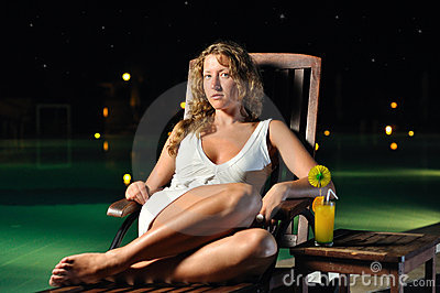 Woman is sitting on chair at poolside at night