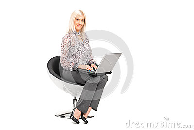 Woman sitting on a chair and working on a laptop