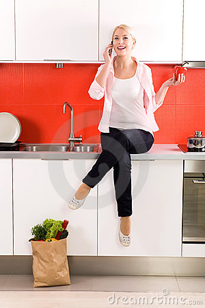 Woman sitting on counter in kitchen