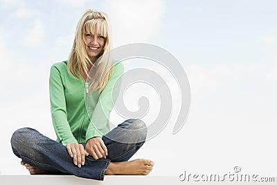 Woman sitting cross legged outside