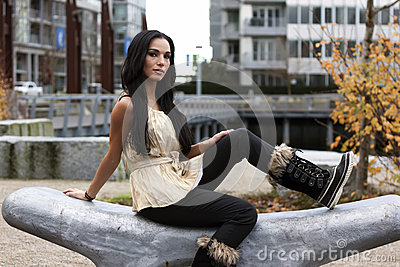 Woman sitting on curvy carved stone bench