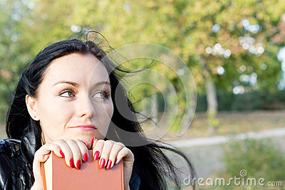 Woman sitting daydreaming with her book