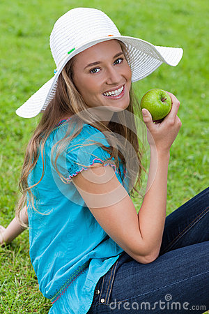 Woman sitting down while eating an apple
