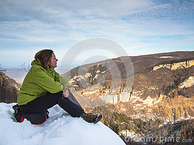 Woman sitting on the edge of the cliff