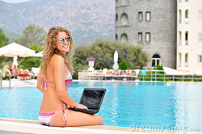 Woman is sitting on the edge of pool with laptop