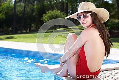 Woman Sitting On Edge Of Swimming In Pool