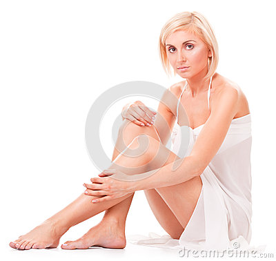 Woman sitting on the floor, showing her slim legs