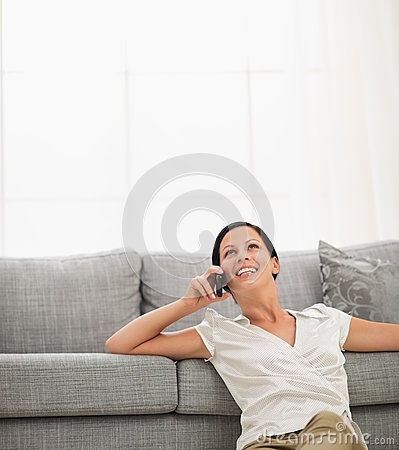 Woman sitting on floor and speaking cell phone