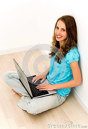 Woman sitting on floor using laptop