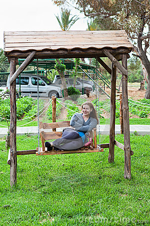 Woman sitting on the garden swing