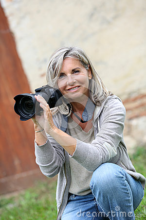 Woman sitting in garden taking pictures