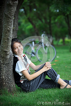 Woman sitting in the green garden with bicycle bac