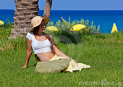 Woman is sitting on green grass near the sea