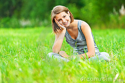Woman sitting on green meadow