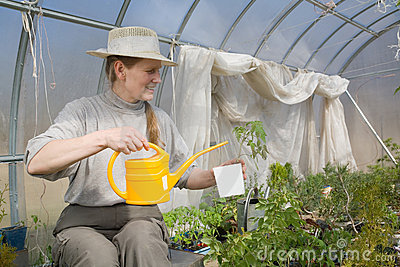 Woman sitting in greenhouse with watering-pot