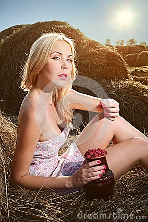 Woman sitting on the hay and eat raspberries