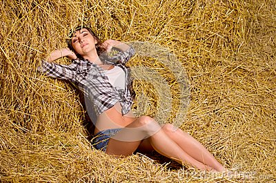 Woman sitting on haystack