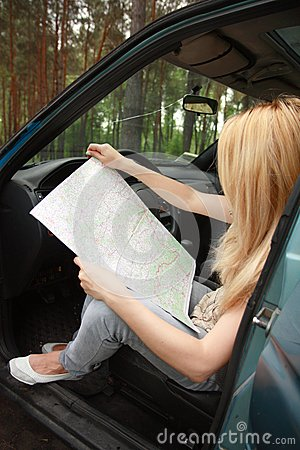 Woman sitting by her car and looking at map