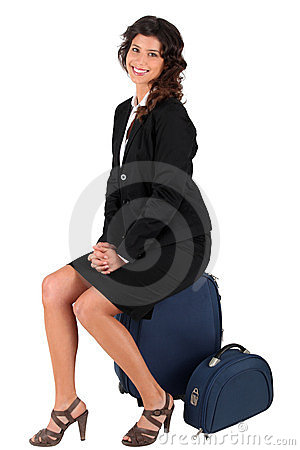 Woman sitting on her suitcase