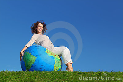 Woman sitting on inflatable globe on lawn Stock Photo