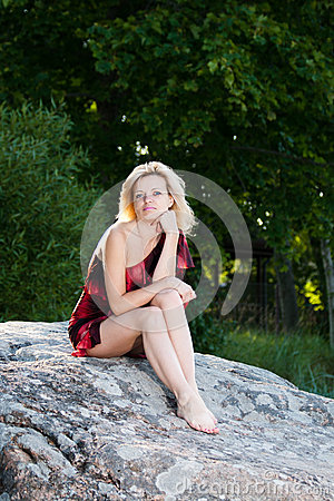 Woman sitting on a large stone