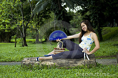 Woman sitting on log with open fan