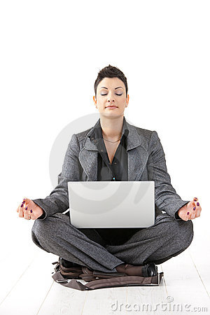 Woman sitting in lotus position with laptop