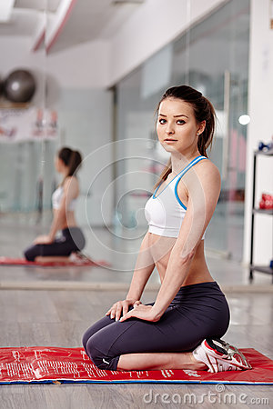 Woman sitting on a mat in gym