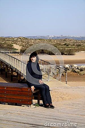 Woman sitting next to a bridge