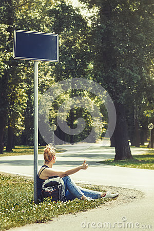 Free Woman Sitting On A Side Of The Road Under The Street Sign, Surrounded By Trees, Hitchhiking Royalty Free Stock Images - 93700009