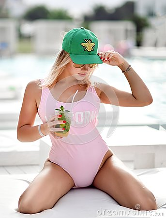 Free Woman Sitting On White Sunbed Near Expensive Swimming Pool In Pink Unicorn Body Vest With Alcohol Mojito Cocktail Royalty Free Stock Photos - 125182638
