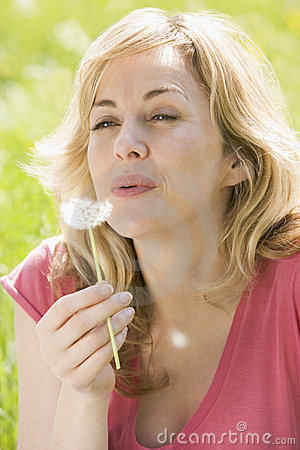 Woman sitting outdoors blowing dandelion head