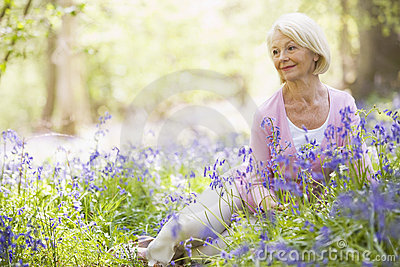 Woman sitting outdoors with flowers smiling