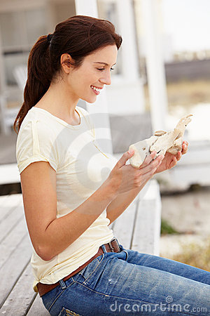 Woman sitting outdoors holding starfish