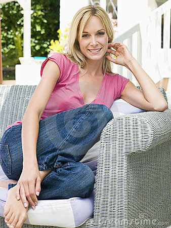 Woman sitting outdoors on patio smiling