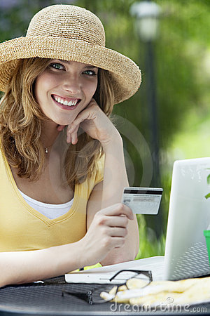 Woman sitting outside using credit card and laptop