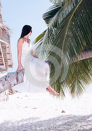 Woman sitting on palm tree on the beach