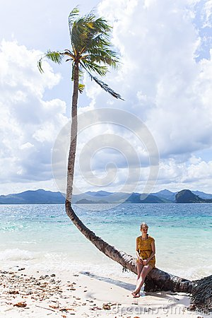 Woman sitting on a palm