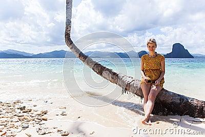 Woman sitting on a palm