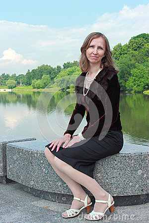 A woman is sitting on the parapet near the pond