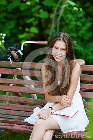 Woman sitting on a park bench with her book