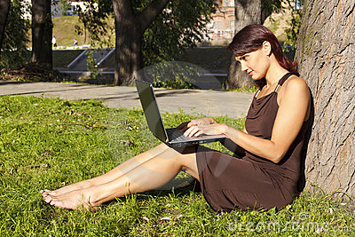 Woman sitting in park with a laptop