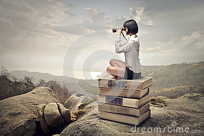 Woman sitting on a pile of books
